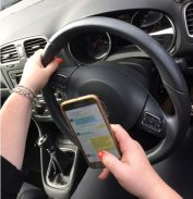 A driver using their mobile phone whilst driving.